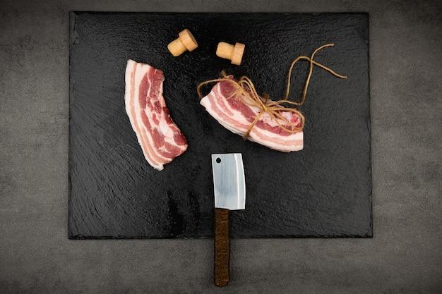 Ci sono coltelli per costole crude e sale e pepe su un tagliere nero