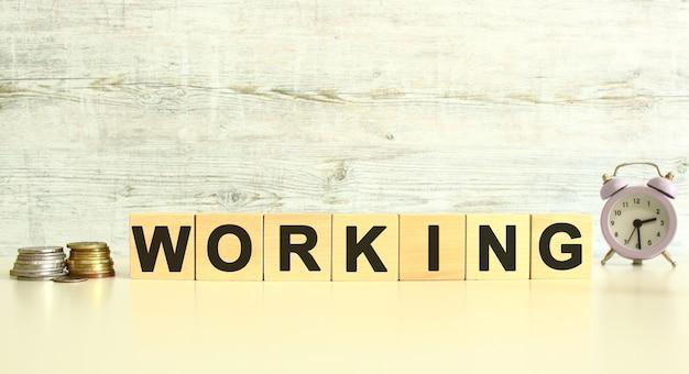 Ci sono sette cubi di legno con lettere sul tavolo accanto alle monete. parola di lavoro. su uno sfondo grigio.