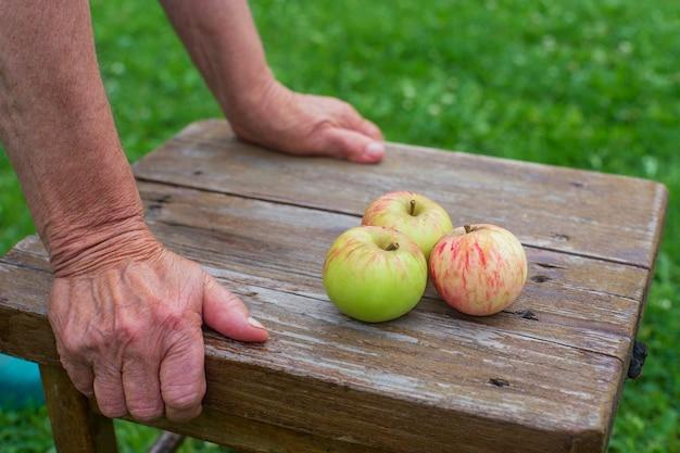 Ci sono tre mele fresche su uno sgabello di legno. raccolta del concetto di cibo sano