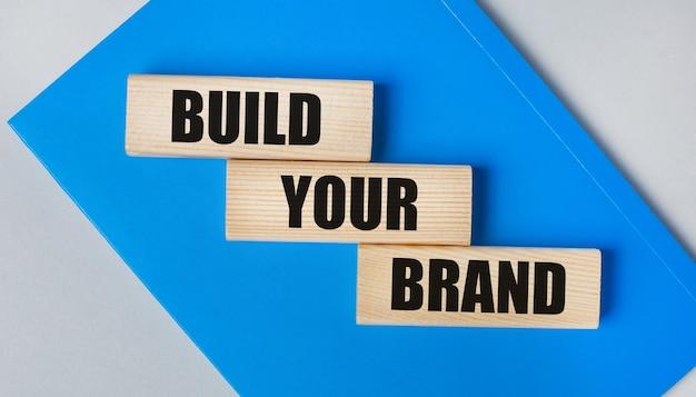 C'è un quaderno blu su uno sfondo grigio chiaro. sopra ci sono tre blocchi di legno con le parole costruisci il tuo marchio.