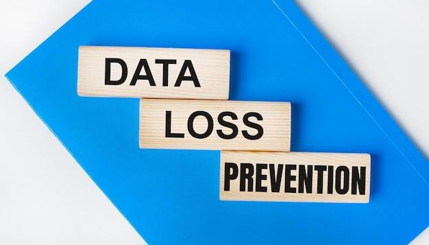 C'è un quaderno blu su uno sfondo grigio chiaro. sopra ci sono tre blocchi di legno con le parole prevenzione perdita di dati.