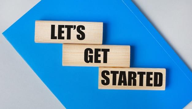 C'è un quaderno blu su uno sfondo grigio chiaro. sopra ci sono tre blocchi di legno con le parole let is get started.
