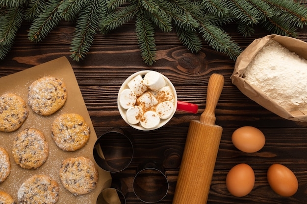 C'è una tazza di cioccolata calda e biscotti di natale su un tavolo di legno