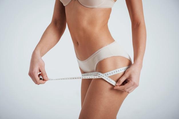 Non c'è limite alla perfezione. l'immagine ritagliata della ragazza in biancheria intima bianca misura i risultati della forma fisica.