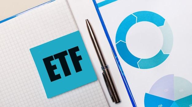 C'è una penna tra il foglietto adesivo blu con il testo etf exchange traded funds e il grafico blu. concetto di affari. vista dall'alto