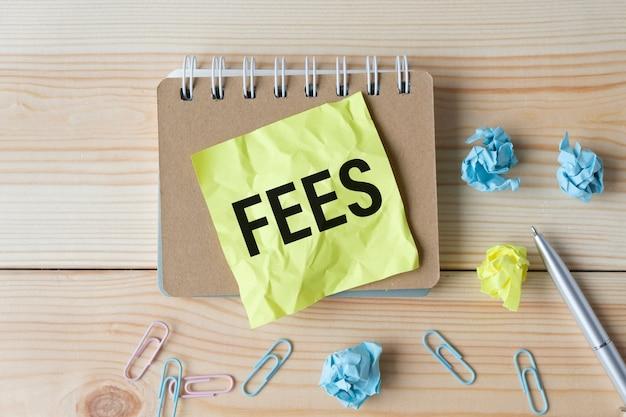 C'è una penna tra il foglietto adesivo giallo con il testo fees. concetto di affari. vista dall'alto
