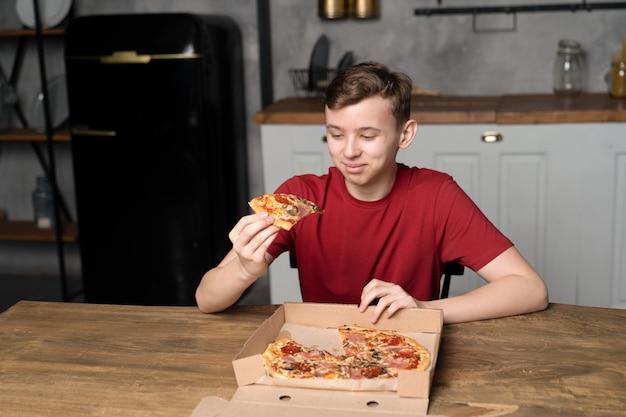C'è la pizza su un tavolo di legno davanti al ragazzo e il gatto ne ha preso un pezzo tra le mani per mangiarlo