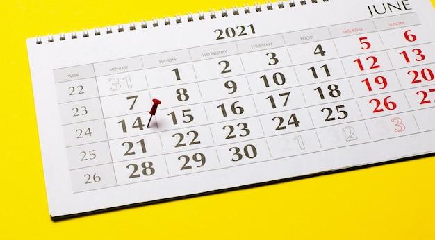C'è un pulsante rosso sul quattordicesimo del foglio del calendario per il 2021. concetto organizzativo