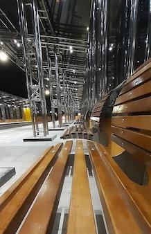 C'è una panchina vuota in legno in stile art nouveau nell'ambiente dei trasporti pubblici. sullo sfondo, strutture in ferro lucente