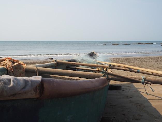 C'è una barca da pesca in legno sulla spiaggia. uno strumento per pescare la popolazione locale