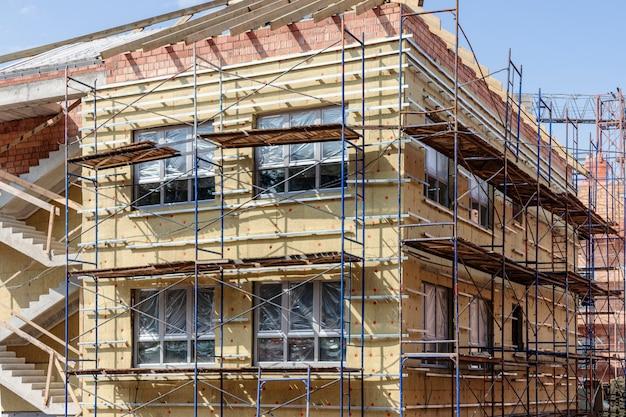 Isolamento termico di una casa in mattoni rossi con lana minerale. l'uso di impalcature durante la costruzione di una casa.