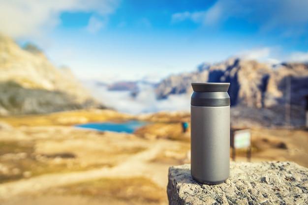 Termo tazza in piedi sulla roccia con vista sulle dolomiti, italia. concetto di viaggio e avventura.