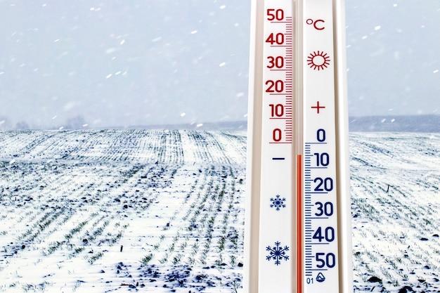 Il termometro sullo sfondo del campo durante la nevicata segna 5 gradi sotto zero