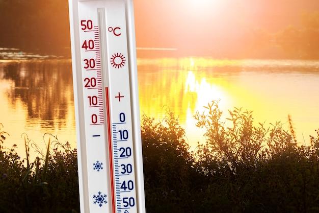 Il termometro sullo sfondo del fiume al tramonto mostra 20 gradi di calore. temperature estive e autunnali la sera