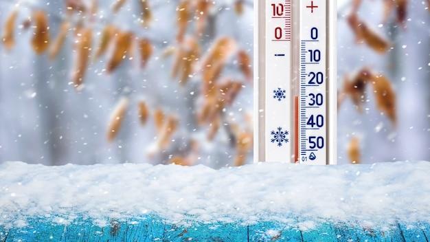 Il termometro su uno sfondo invernale mostra meno 25 gradi