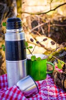 Thermos e una tazza usati in natura