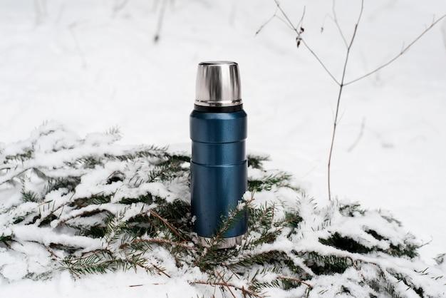 Thermos in piedi sul ramo di pino nella neve. pallone sottovuoto all'aperto. campeggio invernale nel concetto di foresta.