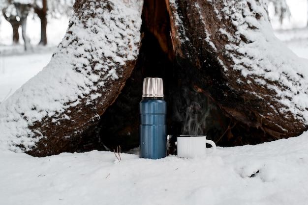 Thermos con tazza di bevanda calda in piedi nella foresta invernale su sfondo di legno.