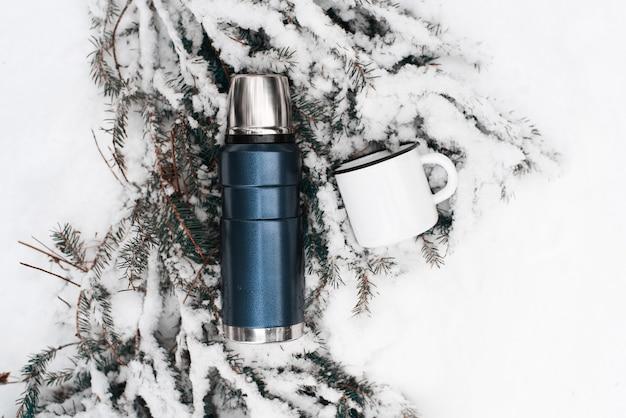 Thermos con una tazza sdraiata su un ramo di pino coperto di neve. vista dall'alto.