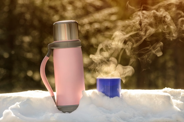 Thermos con una tazza fumante di bevanda calda si trova nella neve. giornata di sole invernale.