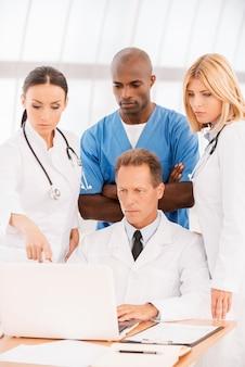 Hanno tutti bisogno di un consiglio esperto. gruppo di medici fiduciosi che discutono di qualcosa mentre guardano insieme il laptop