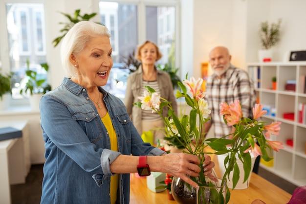 Sono belli. felice donna allegra che tocca i fiori nel vaso ammirando la loro bellezza