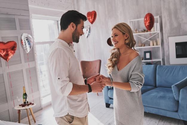 Appartengono insieme. bella giovane coppia che si tiene per mano e si guarda con un sorriso mentre sta in piedi nella camera da letto piena di palloncini