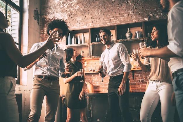 Amano ballare. inquadratura dal basso di giovani allegri che ballano e bevono mentre si godono la festa a casa in cucina