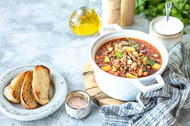 Zuppa densa di carne macinata con pomodori, fagioli, ceci e verdure. cena salutare. copia spazio