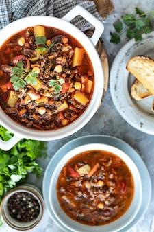 Zuppa di carne macinata spessa con pomodori, fagioli, ceci e verdure.