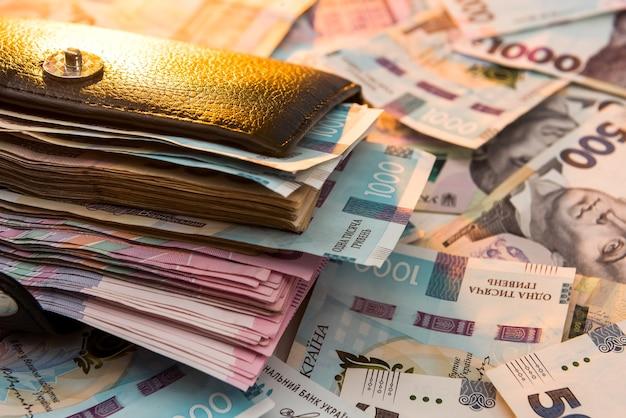 Lo spesso portafoglio da uomo nero carico di denaro si trova sullo sfondo del denaro della grivna ucraina. concetto di risparmio di denaro