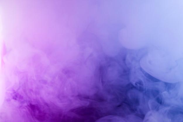 Fumo denso nella luce al neon. luce rosa e blu, trama, sfondo. sfocato. fondo scuro astratto.