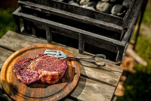 Una spessa bistecca alla griglia all'aperto. un grosso pezzo di carne su una tavola di legno accanto alla griglia. cucinare il cibo