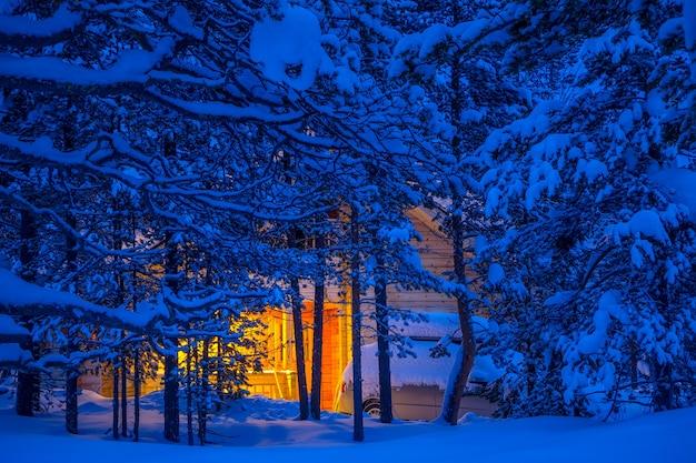 Fitta foresta invernale. sera. tra i rami innevati si vedono una casetta di legno e un'auto