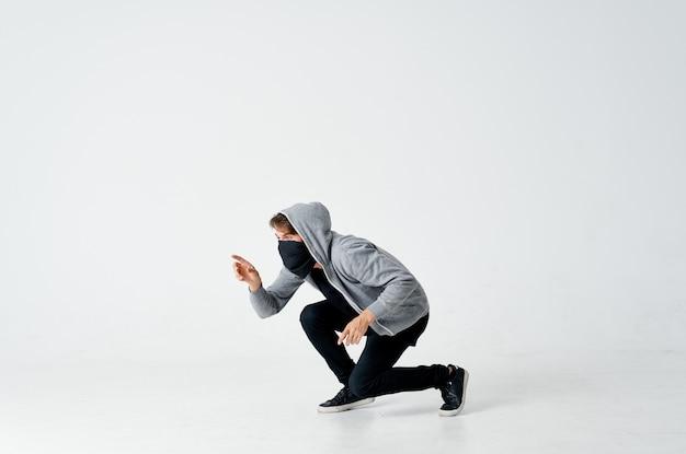 Ladro hacker maschio in una maschera nera e in un cappuccio su uno sfondo chiaro furto