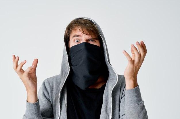 Hacker maschio ladro con una maschera nera e un cappuccio in uno spazio luminoso