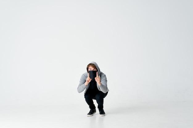 Hacker maschio ladro con una maschera nera e un cappuccio su un furto leggero.