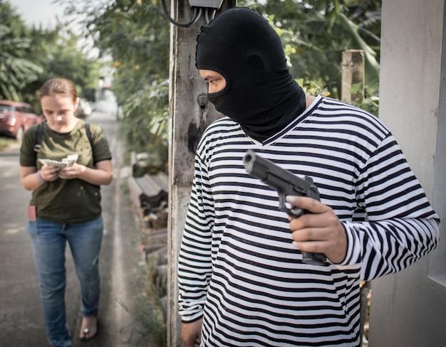 Ladro che ruba soldi dalla donna che cammina sulla strada con la pistola in mano