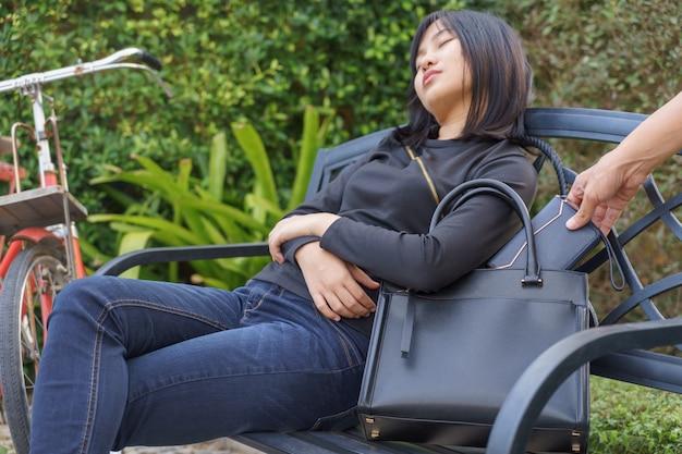 Ladro che cerca di rubare e porta via la borsa a tracolla mentre la donna dorme sulla sedia