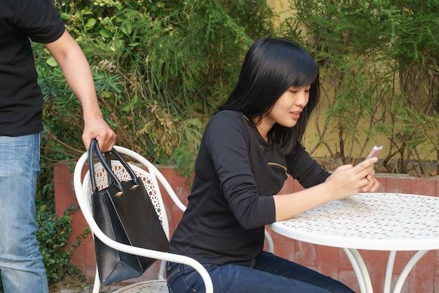 Ladro che cerca di rubare e di portare via la borsa a tracolla mentre la donna usa il cellulare