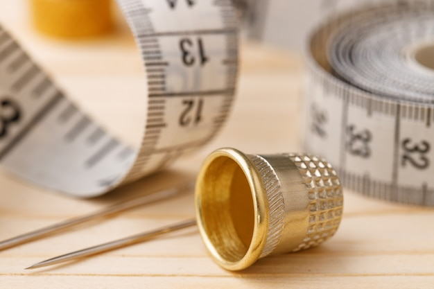 Ditale e nastro di misurazione sulla tavola di legno