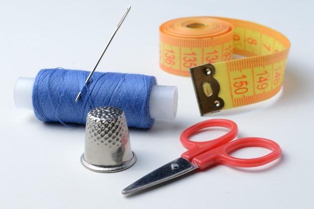 Ditale, ago con rocchetto di filo, forbici e nastro di misurazione su uno sfondo bianco. primo piano.