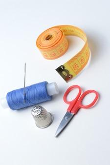 Ditale, ago con rocchetto di filo, forbici e metro su uno sfondo bianco.
