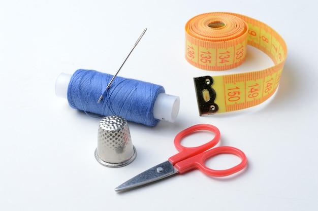 Ditale, ago con rocchetto di filo, forbici e metro a nastro su un bianco
