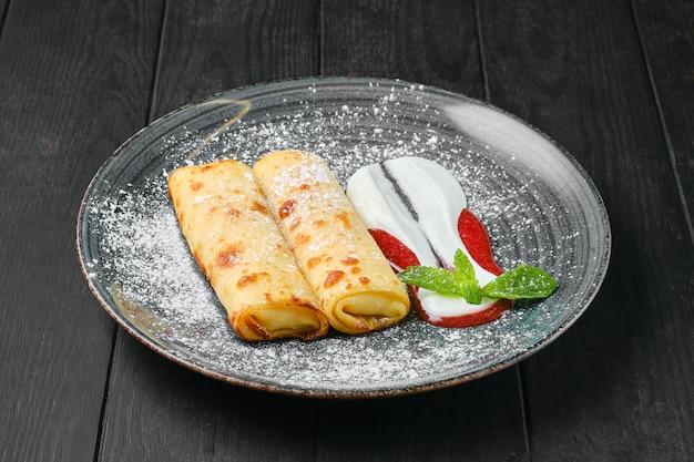 Crepes sottile con ricotta e marmellata di fragole su un piatto