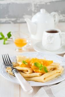 Crepes sottili con salsa di agrumi all'arancia per colazione su superficie leggera. messa a fuoco selettiva