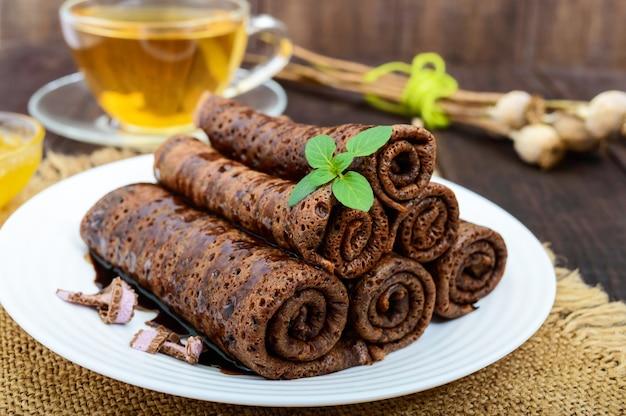Frittelle sottili e delicate al cioccolato, arrotolate, disposte in una pila