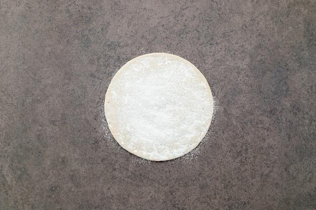Sottile pasta per pizza fatta in casa con farina di frumento sparsa su fondo di cemento scuro.