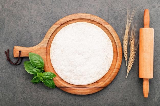 Sottile pasta per pizza fatta in casa con spighe di grano e mattarello impostato su sfondo scuro di cemento.
