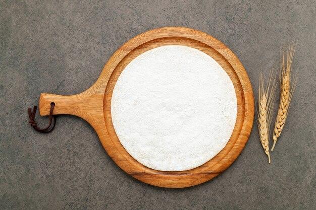 Sottile pasta per pizza fatta in casa con spighe di grano su fondo di cemento scuro.